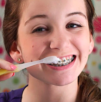 A girl with braces brushing