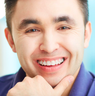 A man smiling with braces