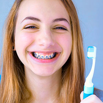 a girl with braces holding a toothbrush